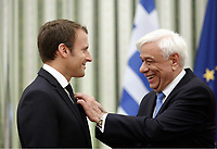 Pictured: (L-R) French President Emmanuel Macron is is awarded the Megalostavros Tou Sotiros (The Great Crucifix Sviour) medal by Greek President Prokopis Pavlopoulos. Thurday 07 September 2017<br /> Re: French President Emmanuel Macron gives a press conference alongside Greek President Prokopis Pavopoulos at the Presidential Mansion during his state visit to Athens, Greece.