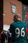 A man in shirt bearing the legend '96' in front of the Kop before the 25th anniversary memorial service to the 1989 Hillsborough disaster at Liverpool Football Club's Anfield Stadium. The Hillsborough stadium disaster led to 96 Liverpool football fans losing their lives in a crush at an FA Cup semi final tie against Nottingham Forest. The families of the victims campaigned against the original verdict of the incident and were rewarded with a new inquiry held in 2014 into events at the match at Hillsborough. Photo by Colin McPherson.