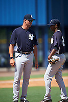 GCL Yankees West pitching coach Arnold Contreras (87) talks with relief pitcher Leonardo Garcia (28) during a game against the GCL Yankees East on August 3, 2016 at the Yankees Complex in Tampa, Florida.  GCL Yankees East defeated GCL Yankees West 12-2.  (Mike Janes/Four Seam Images)