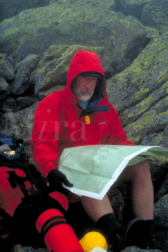 Mountain climber just below the summit of Mt. Jefferson in the Presidential Range of the White Mountains of New Hampshire. Checking his map, the heavy fog is a concern since it is easy to lose the trail in such weather at this altitude, about 5,500 f feet