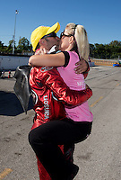 Sep 29, 2013; Madison, IL, USA; NHRA pro stock motorcycle rider Matt Smith (left) kisses wife Angie Smith as they celebrate after winning the Midwest Nationals at Gateway Motorsports Park. Mandatory Credit: Mark J. Rebilas-