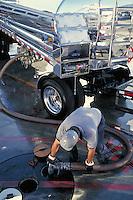 Worker unloading fuel truck to underground storage tank