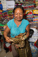 Sukawati, Bali, Indonesia.  Shopkeeper Selling Sarongs and T-shirts.