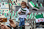 Protesters wave flags of the Syrian opposition during a demonstration in the town of Azaz in the rebel-controlled northern countryside of Syria's Aleppo province, on March 15, 2021, marking ten years since the nationwide anti-government protests that sparked the country's devastating civil war. In the jihadist-dominated stronghold's main city, crowds marched down the street, some waving the opposition's three-star flag, or holding up images of those killed during the conflict. Syria's war has killed more than 388,000 people and displaced millions of Syrians inside the country and abroad. Idlib, whose 2.9 inhabitants have been protected by a ceasefire since March 2020, is one of the few key areas still holding out against the Damascus government. Photo by Nayef ALaboud