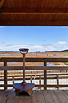 Binoculars at viewpoint on boardwalk over recovering tide flats and salt march after former dikes have been broached to allow nature to recover.  Nisqually River Delta, Nisqually National Wildlife Refuge, Washington State.