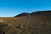 A hiker walks on the barren, moonlike surface inside Haleakala Crater on the island of Maui.