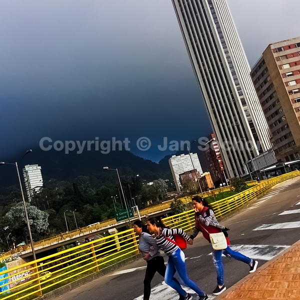 Colombian girls rush to shelter from the coming storm when they walk across the street in Bogotá, Colombia, 2 December 2016.