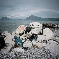 An Afghan refugee sits on graffiti covered stones after he has washed himself in the sea. Patras is home to about 3,000 illegal immigrants. Most of them are Afghans, although there are also some Iranians and Uzbeks. They stop in Patras to try and find passage to various European destinations by hiding in ships, containers and trucks parked in the port. If they are lucky they will make it to their destination. Many of them live in shacks made from cartons, plastic and wood they found on the beach. To shelter from the cold they also squat in abandoned buildings, living without water and electricity. The living conditions are inhumane and unhygienic.