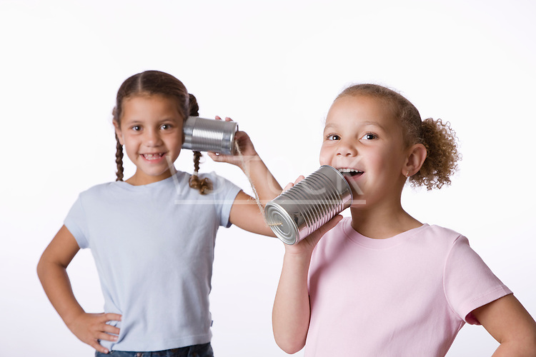 Two girls (6-7, 8-9) playing with tin can phone
