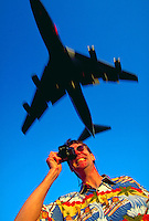Concept image of a tourist - a grinning man wearing a loud shirt and wielding a camera as an airplane passes overhead.