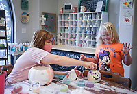"""Melanie Hewins (left) looks at a pumpkin that Addison Powell, 5, (right) created, Sunday, October 11, 2020 at Imagine Studios in Rogers. Imagine hosted a family pumpkin painting party, one of several monthly, themed, art making experiences. In addition, they will start offering """"My Create Crates"""", art kits people can pick up that include art supplies, a canvas, template and a link to an online instructional video for people to follow along with. """"After last spring when I had to switch online to pay my rent, I had to do videos, and over the summer, I thought, I just want to do this bigger,"""" Hewins said of her motivation to start the at-home art kits. People can pick them up or have them shipped. Check out nwaonline.com/2010012Daily/ for today's photo gallery. <br /> (NWA Democrat-Gazette/Charlie Kaijo)"""
