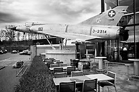 """Switzerland. Canton Zürich. Opfikon. Runway 34 is a restaurant combining the concepts of """"airline"""" and """"restaurant"""". The place is located at the end of the Zurich Airport runway. A derelict Mirage III plane, which was a swiss military fighter aircraft, is fixed on the ground and is used as decoration. The Dassault Mirage III is a family of single-seat, single-engine, fighter aircraft developed and manufactured by French aircraft company Dassault Aviation. It was the first Western European combat aircraft to exceed Mach 2 in horizontal flight. Outside tables on the terrace. Zurich Airport (Flughafen Zürich, IATA: ZRH, ICAO: LSZH) is the largest international airport of Switzerland. 17.01.2020  © 2020 Didier Ruef"""