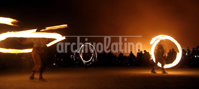 Participants of the event put on a fire show in Burning Man festival, Nevada, USA, September 4, 2005..Born in Argentina, photographer Ivan Pisarenko in 2005  decided to ride his motorcycle across the American continent. While traveling Ivan is gathering an exceptional photographic document on the more diverse corners of the region. Archivolatino will publish several stories by this talented young photographer..Closer look at  Ivan's page www.americaendosruedas.com....
