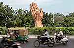 """13 September, 2013, Ahmedabad, Gujarat INDIA :  Motorists drive past a statue of hands in a traditional Hindu 'Namaste"""" greeting in Ahmedabad. Chief Minister of Gujarat , Narendra Modi, has been announced as the Prime Ministerial candidate for the opposition BJP party in the Indian general elections slated for 2014.   Mr.Modi has been a controversial figure since his involvement in the 2002 Gujarat riots where a train full of Hindu pilgrims was attacked by Muslims returning from a disputed temple site in Ayodhya.  In retaliation some estimate up to 2000 Muslims lost their lives in communal violence.   Mr. Modi is alleged to have condoned the violence despite being cleared of any allegations by a Special Investigation Team (SIT) appointed by the Supreme Court of India. Picture by Graham Crouch/New York Times"""