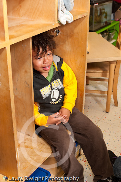 Education preschool 4-5 year olds frustrated angry boy crying sitting in cubby vertical