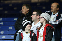 Something in the opposite stand catches the attention of a young Swansea City Fan as everyone else looks in the opposite direction whilst they watch the Barclays Premier League match between Everton and Swansea City played at Goodison Park, Liverpool
