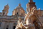 17th century Fiumi Fountain in the Piazza Navona with the Sant'Agnese in Agone Baroque church in the background in Rome, Italy