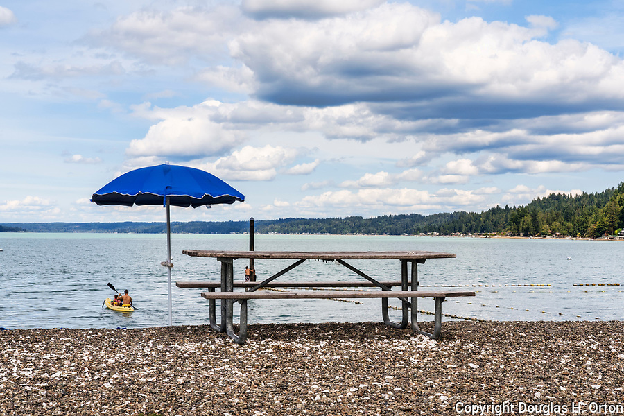 Picnic table, kayakers and swimmers at Twanoh State Park, Washington, USA