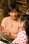 Education preschoool children ages 3-5 female teacher reading picture book to two girls vertical