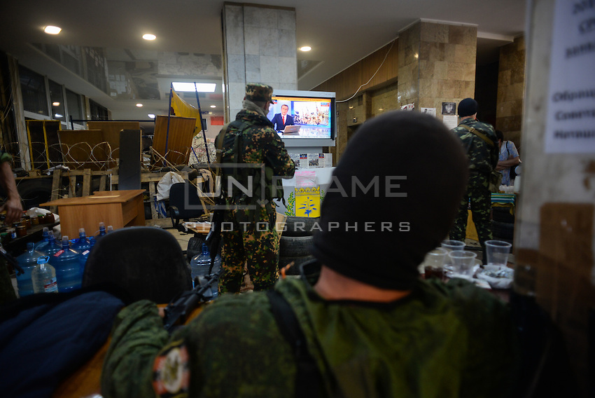 """Member of special pro-Russian battalion """"Vostok"""" watching the Russia 24 news channel."""
