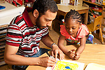 Education Preschool Headstart 3-4 year olds young male teacher scribing writing description of drawing done by girl