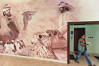 "United Arab Emirates (UAE). Dubai. The Falcon & Heritage Sports Centre is a place full of shop selling falcons and all equipment needed for falconry. It has also a museum dedicated to Falconry which has been practised in the UAE for centuries and continues to play an integral part in Arab desert life. On the wall, a drawing of falconers and hawks hunting in the desert. A shop's worker comes out the restroom and dries his hands with paper. Falcons are birds of prey in the genus Falco, which includes about 40 species. Adult falcons have thin, tapered wings, which enable them to fly at high speed and change direction rapidly. Additionally, they have keen eyesight for detecting food at a distance or during flight, strong feet equipped with talons for grasping or killing prey, and powerful, curved beaks for tearing flesh. Falcons kill with their beaks, using a ""tooth"" on the side of their beaks. The United Arab Emirates (UAE) is a country in Western Asia at the northeast end of the Arabian Peninsula. 16.02.2020  © 2020 Didier Ruef"