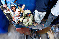 A mother and baby are among a group of passengers that crowd onto a small space between two carriages on the outside of an inter-city train from Dhaka to Sylhet, a journey of some 350 kilometres. In Bangladesh many people ride on the roofs of trains as frequently that is the only space available. For others, the fares are too high and can be avoided or reduced by travelling on the roof. However, this practice also leads to regular accidents, many of them fatal....