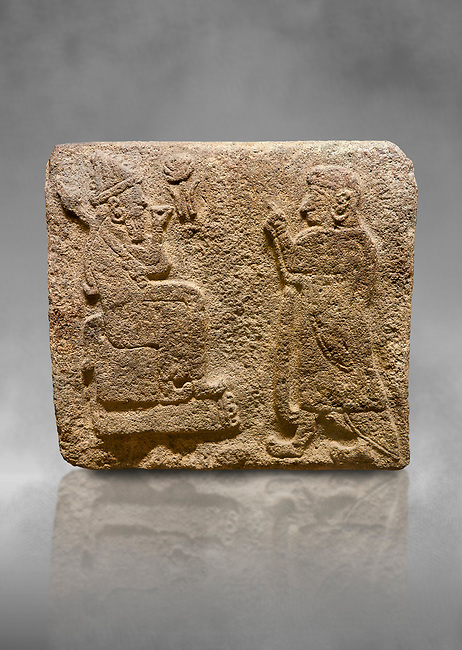 Alaca Hoyuk Sphinx Gate Hittite monumental relief sculpted orthostat stone panel. Andesite, Alaca, Corum, 1399 - 1301 B.C. Anatolian Civilisations Museum, Ankara, Turkey.<br /> <br /> Figure with a sharp and horned headdress (probably a god) sitting on a stool with a short backrest, with a figure (probably the figure of a king) worshipping to it. Both figures wear a large and ring-shaped earring. Among them is a hieroglyph, the symbol of divinity.<br /> <br /> Against a grey art background.
