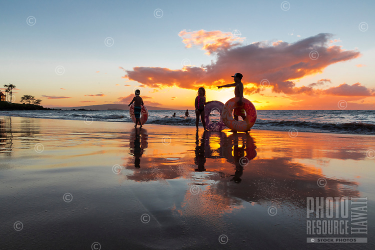 At sunset, many children play in the warm waters of Wailea Beach, Maui.