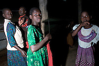 Young girls socialize at the Doctors Without Borders (MSF; Medecins Sans Frontieres) tent compound. This compound is one of the few places children, known as Night Commuters, can find protection every  night to avoid being abducted by the Lords Resistance Army (LRA) in Northern Uganda. The LRA is primarily made up of abducted youth. Night Commuters find much more than safety in the compounds, they also find friendships, activity and fellowship. Tens of thousands of children, on average, make this exodus every evening. The war in Northern Uganda has been transpiring for two decades. Lachor, Gulu District, Uganda, Africa. December 2005 © Stephen Blake Farrington