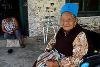 NEPAL Pokhara, tibetan refugee camp, old woman with praying necklace in wheelchair / tibetisches Fluechtlingslager Prithivi, alte Tibeterin bei einem Gebet mit Gebetskette im Rollstuhl