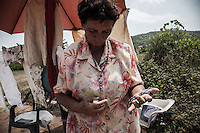 A souvenir and rosaries vendor. Many vendors on the pathway between Bijakovici and Medjugorje are of Muslim faith.<br /> Bijakovici, Medjugorje, Bosnia and Herzegovina. July 2012