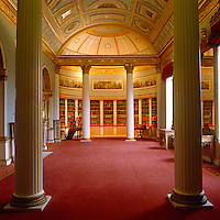 In the grand library at Kenwood House books are arranged in curved bookcases beneath a barrel-vaulted ceiling decorated with painted panels
