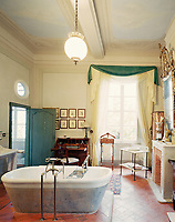 The bathroom has the same, cool terracotta tiles that are a feature of the property and is dominated by a vast free-standing bath on a raised platform