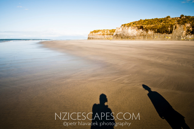Shadows of two people on Carters Beach in Westport - Buller Region, Central West Coast, New Zealand