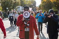"""Mehrere tausend Menschen protestierten am Sonntag den 25. Oktober 2020 in berlin gegen die Coronaregeln der Bundeslaender und der Bundesregierung. Unter ihnen etliche Anhaenger von Verschwoerungstheorien, Impfgegner und Rechtsextreme. Sie hielten Schilder auf denen der Virologe Prof. Christian Drosten und der ehemalige Microsoft-Chef Bill Gates als Straeflinge abgebildet waren, zum Widerstand gegen einen """"Corona-Faschismus"""" aufgerufen und Impfungen als """"Menschenversuche"""" bezeichnet wurden. Weiter wurde ein Ende der Test gefordert und die zweite Corona-Welle als normale Herbstgrippe bezeichnet wurde.<br /> Sie zogen ohne Genehmigung in mehreren Zuegen durch den Bezirk Mitte, zum Teil ohne Polizeibegleitung. Der Polizei gelang es erst nach etwa einer Stunde die Demonstrantionszuege zu begleiten.<br /> Vereinzelt kam es am Rande zu Gegenprotesten, denen Srechchoere """"Nazis raus!"""" und """"Reiht euch ein!"""" entgegen gerufen wurde.<br /> Im Bild: Der Demonstrant traegt hinten auf seiner Jacke ein DDR-Emblem und an seinem Megafon hat er ein """"Eisernes Kreuz"""" geklebt.<br /> 25.10.2020, Berlin<br /> Copyright: Christian-Ditsch.de"""