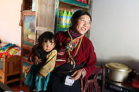 A Tibetan woman and her child in their home in the town of Zaduo, in the far interior of the Tibetan Plateau, in western China. Relocation communities been created to house nomadic herders moved from the highland grasslands. The nomads have been blamed for contributing to the deterioration of the grasslands, so have been moved, sometimes forcibly, into newly built towns that can be found across the plateau.