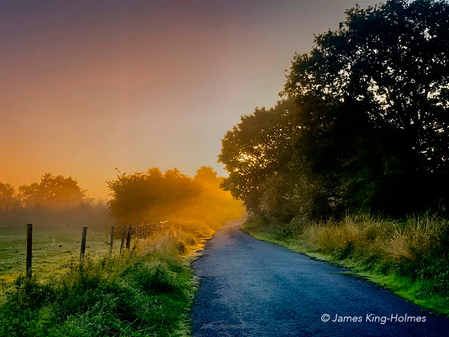 Sun rising over the abandoned main road in the village of Fyfield, Oxfordshire, UK. The trunk  road from Oxford to Swindon once ran through the village but a bypass was created in 197xx which cut off the village and the old road is now not used except for cyclists and pedestrians. A low morning sun illuminates mist on the abandoned main road in the village of Fyfield, Oxfordshire, UK. The trunk  road from Oxford to Swindon once ran through the village but a bypass was created in 197xx which cut off the village and the old road is now not used except for cyclists and pedestrians.