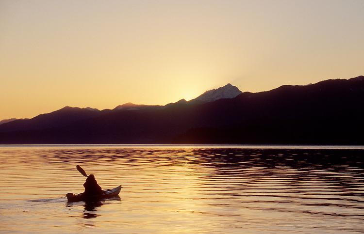 Sea Kayaking, Hood Canal, Woman sea kayaker paddles toward sunset,  Olympic Mountains, Puget Sound, Washington State, Pacific Northwest, USA, .