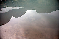 Mountains are reflected in runoff from Grinnell Glacier in Glacier National Park, Montana, USA.