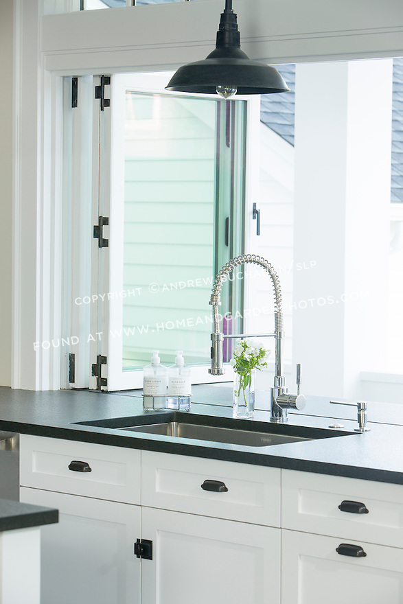 Dark stone countertops and white cabinetry create a crisp look in a newly remodeled kitchen.