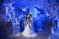 Yakutsk, Yakutia, Russia, 19/08/2011..Newly-weds Nadezhda and Vasily Fedorov with an ice sculpture of reindeer herders inside the Permafrost Kingdom, an underground tourist attraction inspired by the extreme cold of Yakutia. The 150 metre deep complex of tunnels in the Russian permafrost are decorated with ice sculptures, a wolf-fur covered throne, an office complete with the coolest computer and telephone, a children's slide and other ingenious creations - all hewn from blocks of ice.