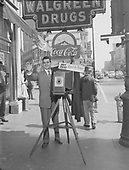 "0405-M01 E. Hayes poses with 8x10"" view camera on tripod. Sign says ""Hey Folks, Watch The Birdie"". He is in front of Walgreen Drugs in Dallas, Texas."