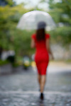 Out of focus portrait of the back of a woman in a red elegant dress with an umbrella walking away in the rain on a cobbled city street