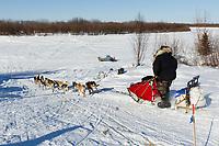Paul Johnson runs down the road as he leaves Shageluk  on Saturday during Iditarod 2011