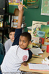 Education Elementary Public school grade 4 class with science specialist male student with determined expression raising hand to answer question vertical