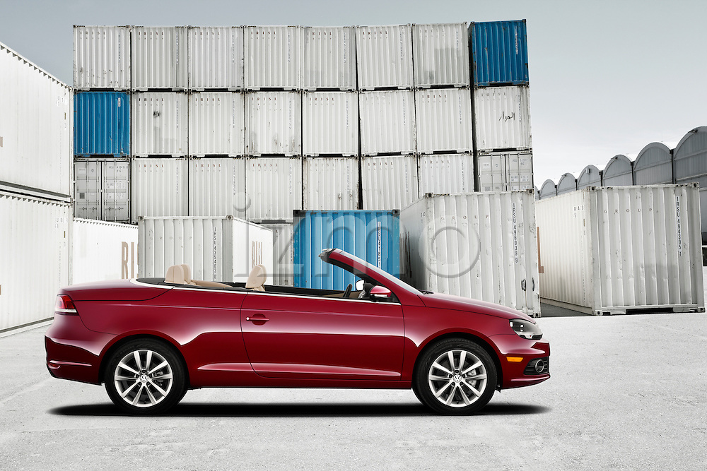 One red 2011 Volkswagen EOS Komfort outdoors at shipping port.