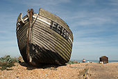 Decaying fishing boats and fishermen's huts on the shingle beach at Dungeness, Kent.
