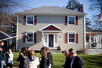 Members of the media watch as Republican presidential candidate Mitt Romney, former governor of Massachusetts, walks through a neighborhood and knocks on the doors of likely primary voters in Manchester, New Hampshire, on Sat. Dec. 3, 2011. The neighborhood traditionally votes Republican.