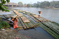 Indian labourers manouver a pontoon of bamboo poles toward markets using the flow of a river at Chakmaghat, some 60 kms from Agartal, capital of the Northeastern state of Tripura, India.<br /> <br /> A vast population of mainly tribals in the northeastern region of India depend on bamboocultivation and trading to earn a loving. Bamboo is used 4 multiplt purposes like constructing dwelling, traditional utensils and crafts, and decorative items are also finding an increasing demand in foreign markets.The technique is often used by smugglers to smuggle bamboo to Bangladesh as all rivers of Tripura flow into neighbouring country of Bangladesh.<br /> <br /> <br /> PHOTO : agence Quebec Presse<br />  - Abhisek Saha